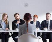 jonge vrouw op de rug gezien in sollicitatiegesprek