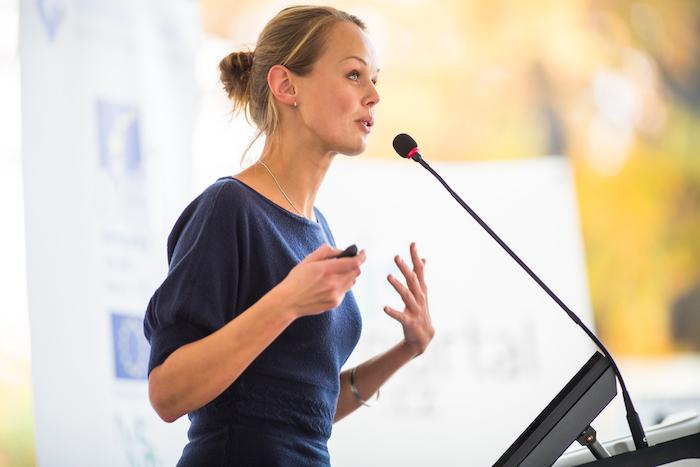 Vrouw, die na stemcoaching een overtuigende presentatie geeft