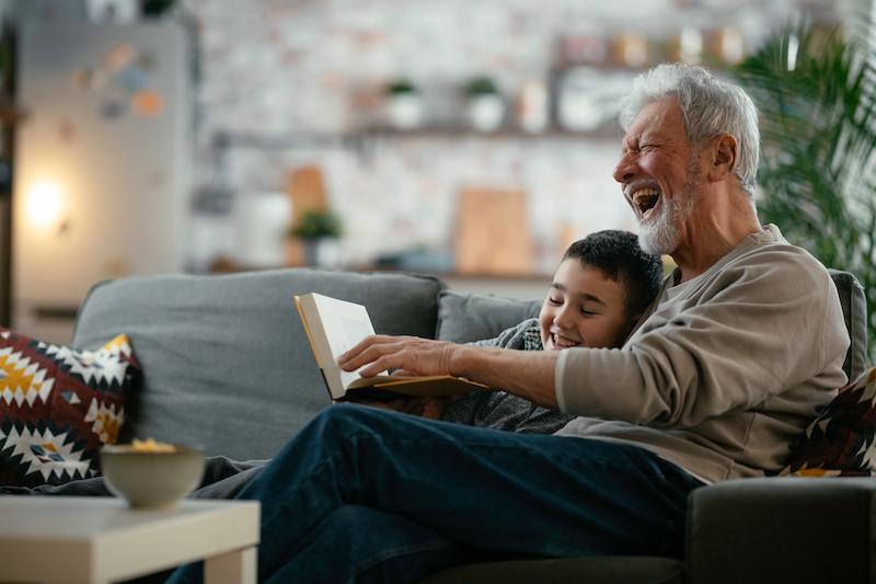 Grootvader en kleinzoon hebben veel plezier bij het voorlezen op de bank